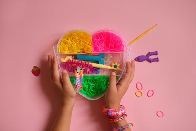 Des élastiques pour tisser des bracelets dans une boîte en forme de cœur sont tenus par un enfant