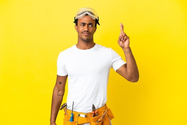 Un électricien afro-américain sur un mur jaune isolé avec les doigts qui se croisent et qui souhaitent le meilleur