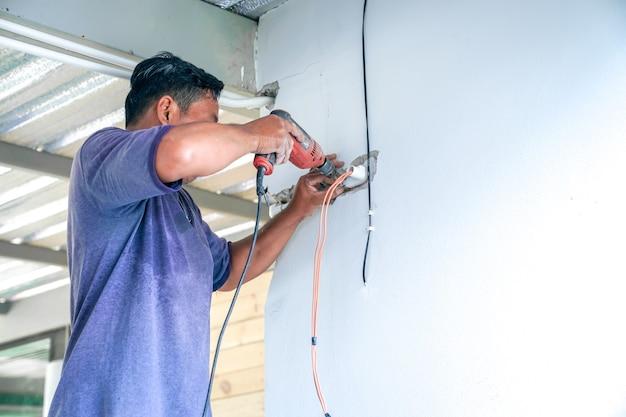 Un électricien asiatique tente de réparer l'interrupteur et le fil électrique sur le mur détruit.