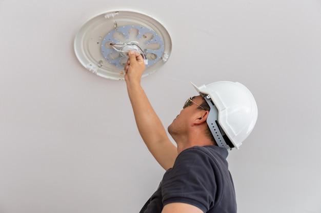 Électricien avec casque blanc vérifiant l'éclairage au plafond dans la maison, concept de technicien.