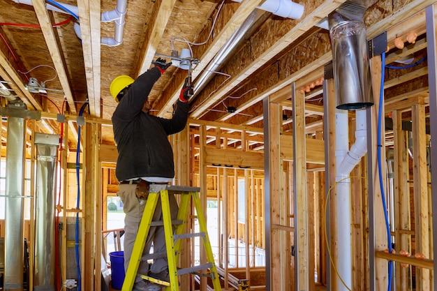Électricien clouant une lampe au plafond