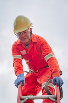 Un électricien en combinaison de sécurité grimpe sur le toit.
