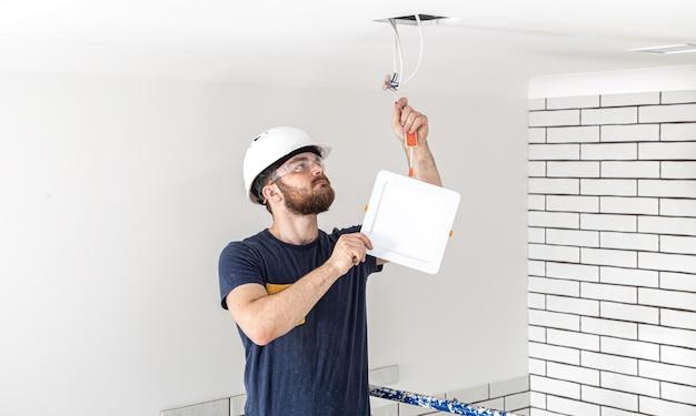 Électricien constructeur avec barbe travailleur dans un casque blanc au travail, installation de lampes en hauteur. professionnel en salopette avec une perceuse sur le site de réparation.