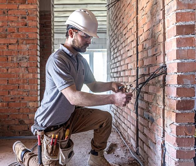 Un électricien en construction coupe un câble de tension lors d'une réparation