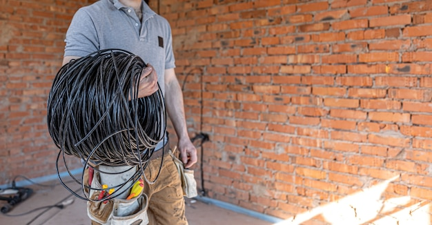 Un électricien dans un casque regarde le mur tout en tenant un câble électrique