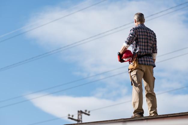 Électricien debout sur le toit