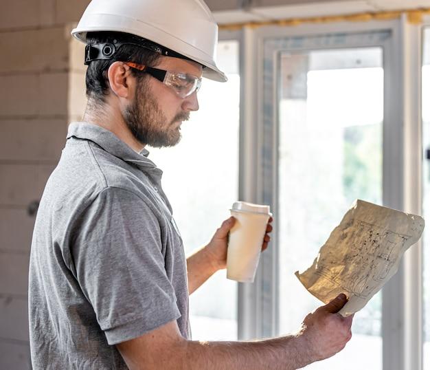 Un électricien étudie un dessin de construction avec un café à la main
