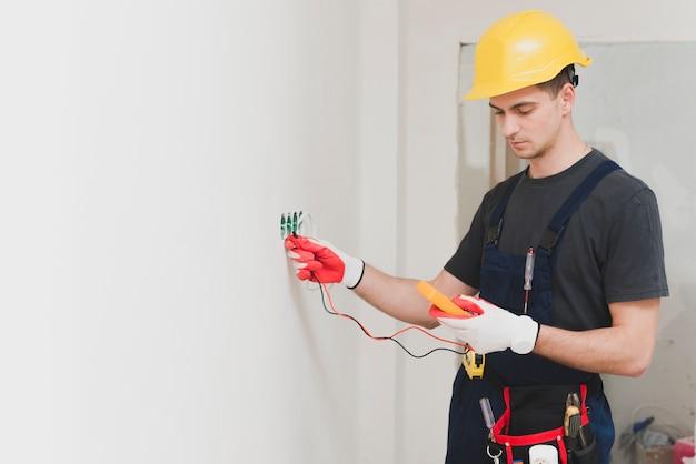Électricien faisant mesure à la prise
