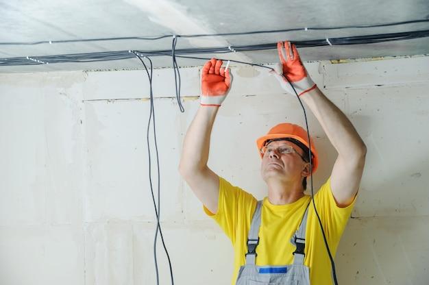 L'électricien fixe un câble électrique au plafond.