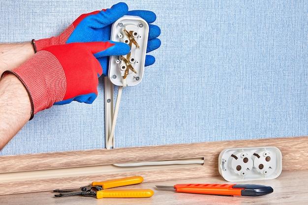 Un électricien en gants de protection installe une prise murale électrique.