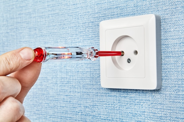 L'électricien insère un tournevis de testeur avec un contact et une lampe led rouge dans le trou d'une prise électrique pour déterminer le fil de phase.