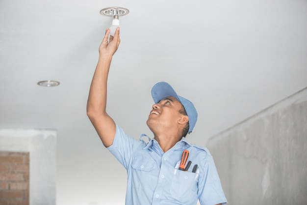 Électricien installant une ampoule dans le downlight