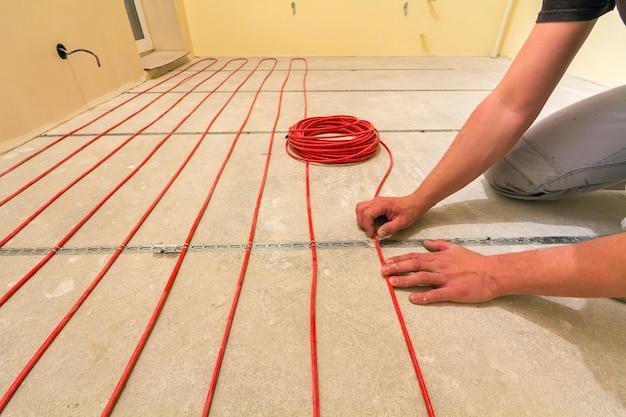 Électricien installant un câble de chauffage électrique rouge sur un sol en ciment dans une pièce inachevée.