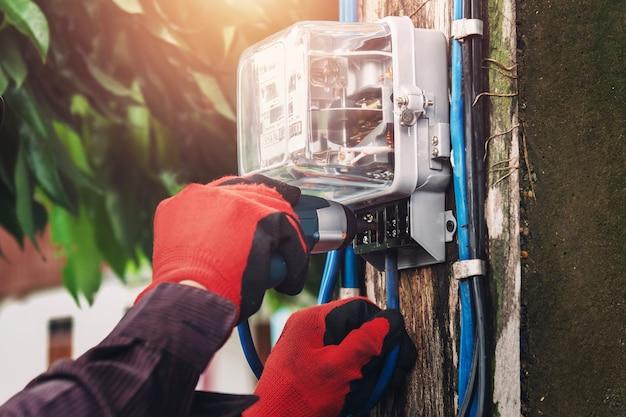 Électricien installant un compteur d'eau à la maison