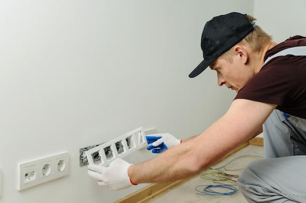 Un électricien installe un cadre décoratif.