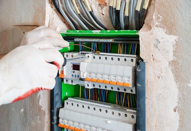 L'électricien installe les fusibles dans le coffret électrique