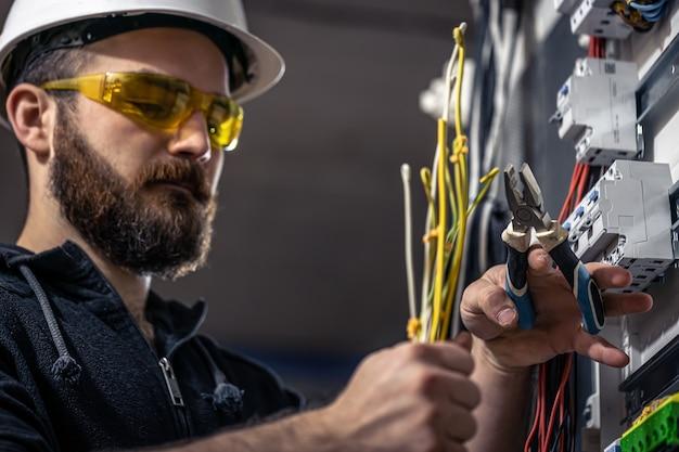 Un électricien masculin travaille dans un standard avec un câble de raccordement électrique
