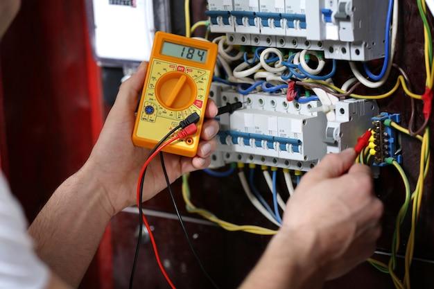 Électricien mesurant la tension dans le tableau de distribution, gros plan