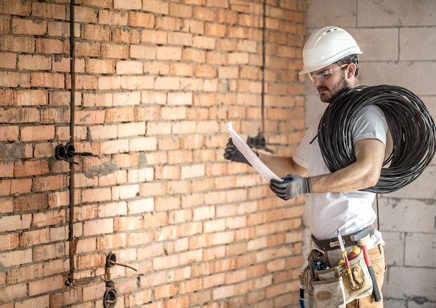 Électricien avec des outils de construction, en regardant les dessins sur le chantier de construction. réparation et bricoleur.