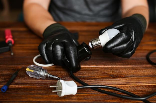 Un électricien professionnel change d'ampoule, l'homme vissant une nouvelle ampoule au plafond