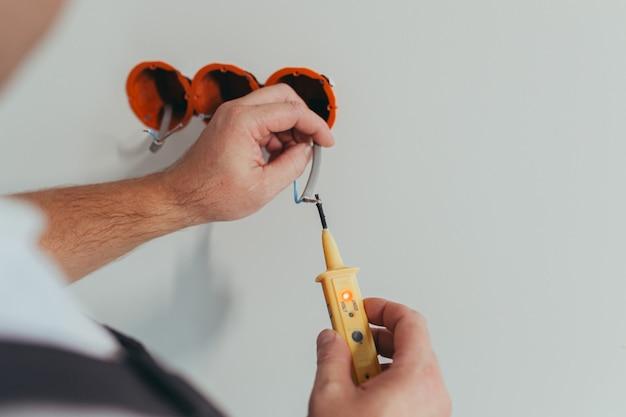Un électricien professionnel ouvrier monte une prise électrique dans l'appartement après réparation, photo en gros plan de l'installateur