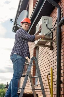 Électricien professionnel réparant le climatiseur sur le mur extérieur du bâtiment