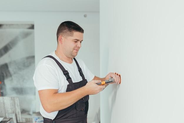 L'électricien professionnel de travailleur masculin installe la prise électrique dans l'appartement après réparation