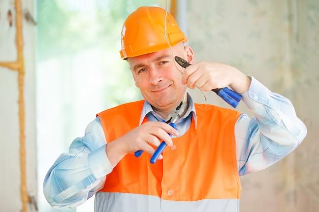 Électricien réparant le câblage du plafond dans la maison