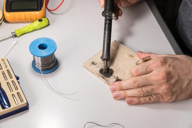 L'électricien technicien prépare le fer à souder à la colophane pour fonctionner