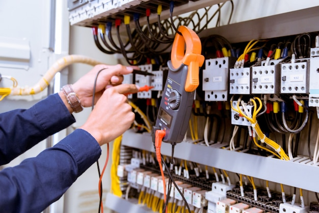 Électricien testant le courant électrique dans le panneau de commande.