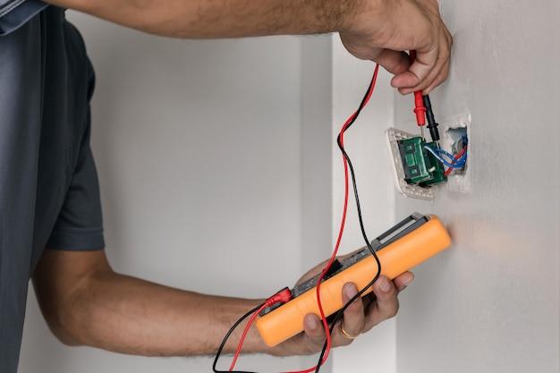 Électricien utilise un compteur numérique pour mesurer la tension à la prise de courant sur le