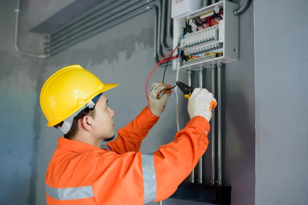 Des électriciens asiatiques inspectent les systèmes électriques des bâtiments