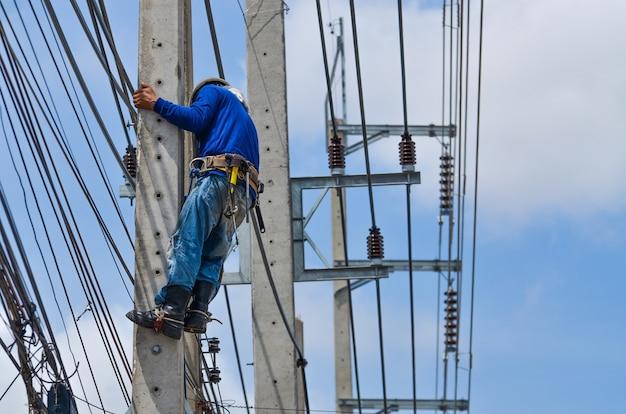 Des électriciens grimpent sur des poteaux électriques pour installer et réparer des lignes électriques.