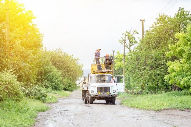 Électriciens travaillant sur des poteaux, un groupe de travailleurs dans des véhicules spéciaux
