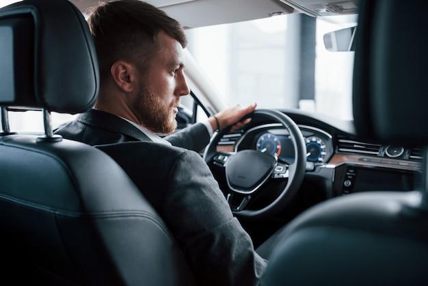 Élégance et beauté. homme d'affaires moderne essayant sa nouvelle voiture dans le salon automobile