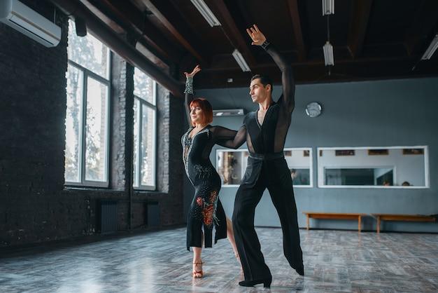 Élégance homme et femme en costumes sur la formation de danse ballrom en classe. partenaires féminins et masculins sur un couple professionnel dansant en studio