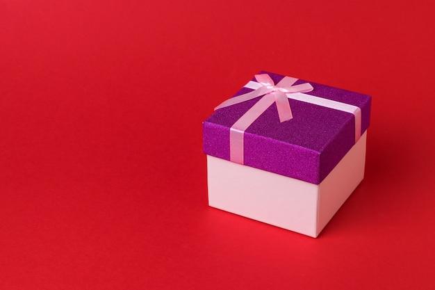 Élégant beau coffret cadeau avec un arc sur le rouge. un cadeau de vacances.
