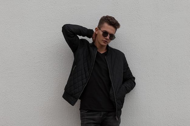 Élégant beau jeune homme hipster avec des lunettes de soleil dans des vêtements noirs à la mode pose près du mur gris