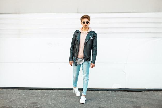 Élégant beau jeune homme avec des lunettes de soleil dans une veste en cuir noir, un jean à la mode bleu et des baskets à la mode blanches près d'un mur en métal blanc