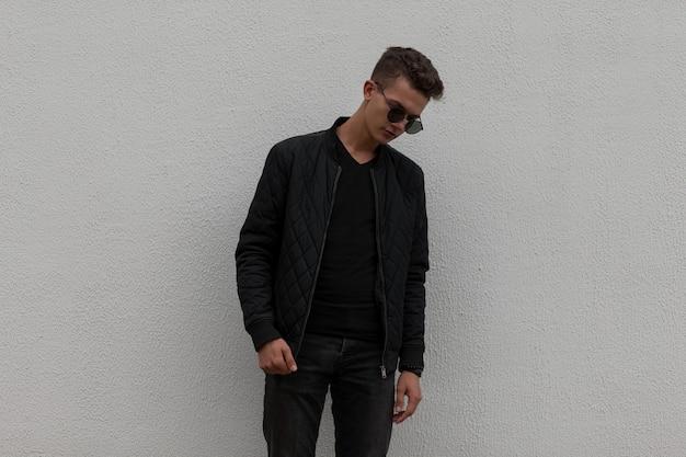 Élégant beau jeune homme avec des lunettes de soleil dans des vêtements à la mode noirs avec une veste près d'un mur gris dans la rue
