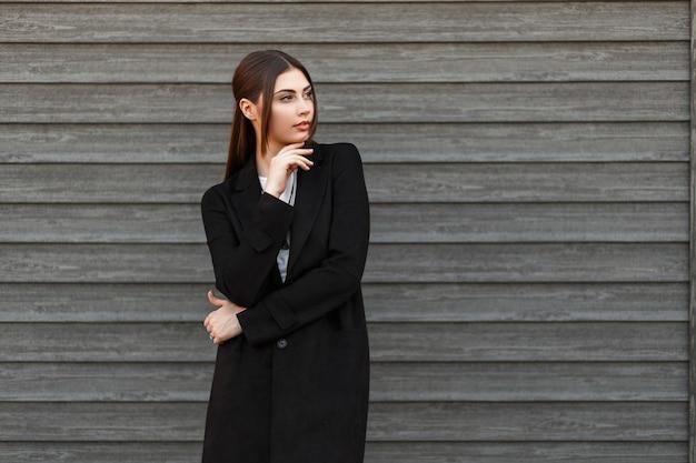 Élégant beau modèle femme en manteau noir posant près de maison en bois vintage