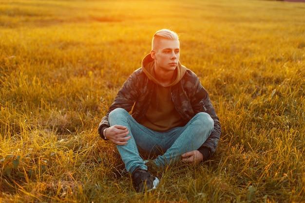 Élégant bel homme dans une veste militaire avec un jean assis sur l'herbe au coucher du soleil