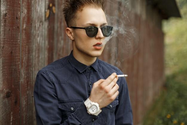 Élégant bel homme fumant une cigarette près d'un mur vintage