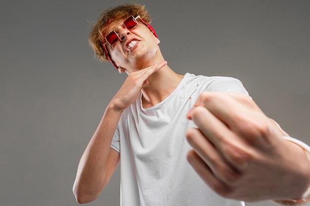 Élégant blond avec des lunettes montre que quelqu'un se sentira mal sur un mur gris