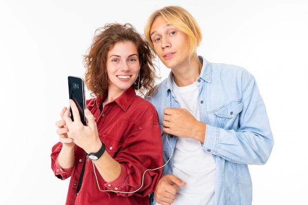 Élégant couple caucasien amoureux écouter de la musique et faire selfie isolé sur mur blanc