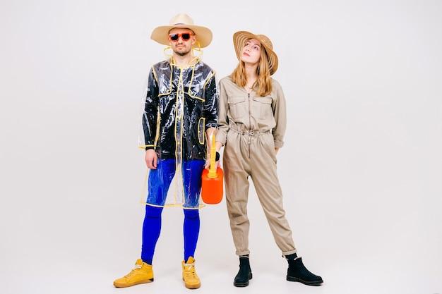 Élégant couple d'homme et femme en chapeaux de paille posant avec arrosoir