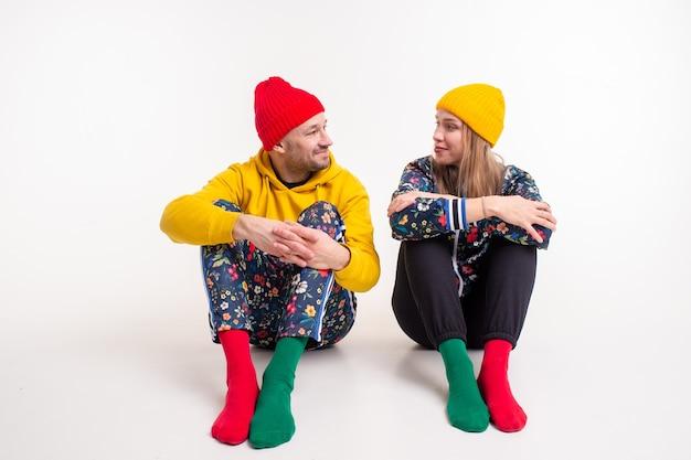 Élégant couple d'homme et femme dans des vêtements colorés posant sur un mur blanc