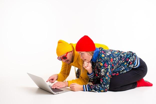 Élégant couple d'homme et femme dans des vêtements colorés en regardant l'écran de l'ordinateur portable