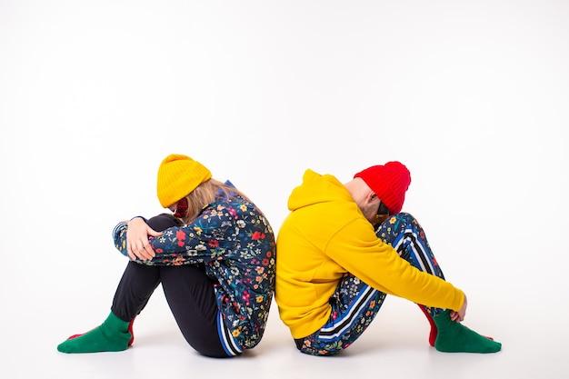 Élégant couple d'homme et femme en vêtements colorés posant