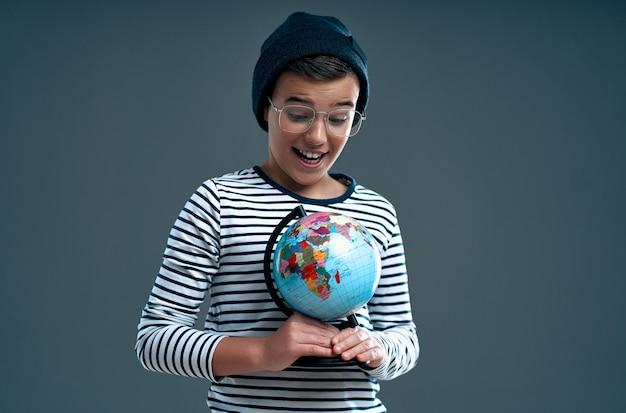 Élégant écolier d'enfant intelligent en chapeau et lunettes se penche sur le globe isolé sur un gris.